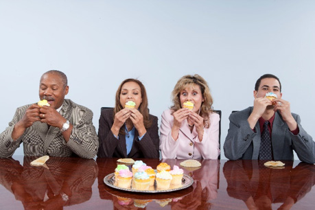 Employees eating cupcakes during a meeting